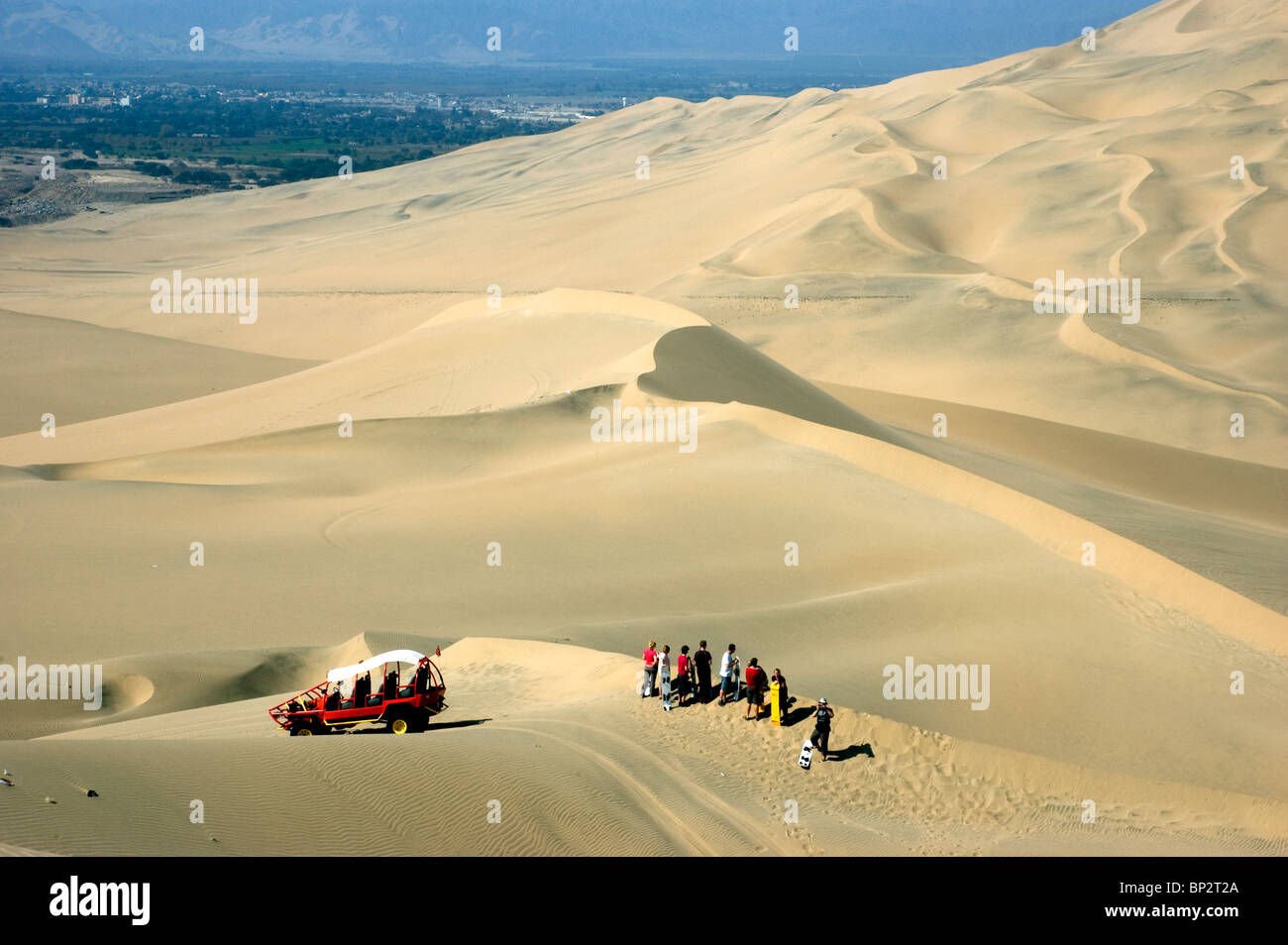 Dune buggies with tourists sand boarding on the vast desert sand dunes near the Huacachina Oasis, Ica, Peru. - Stock Image