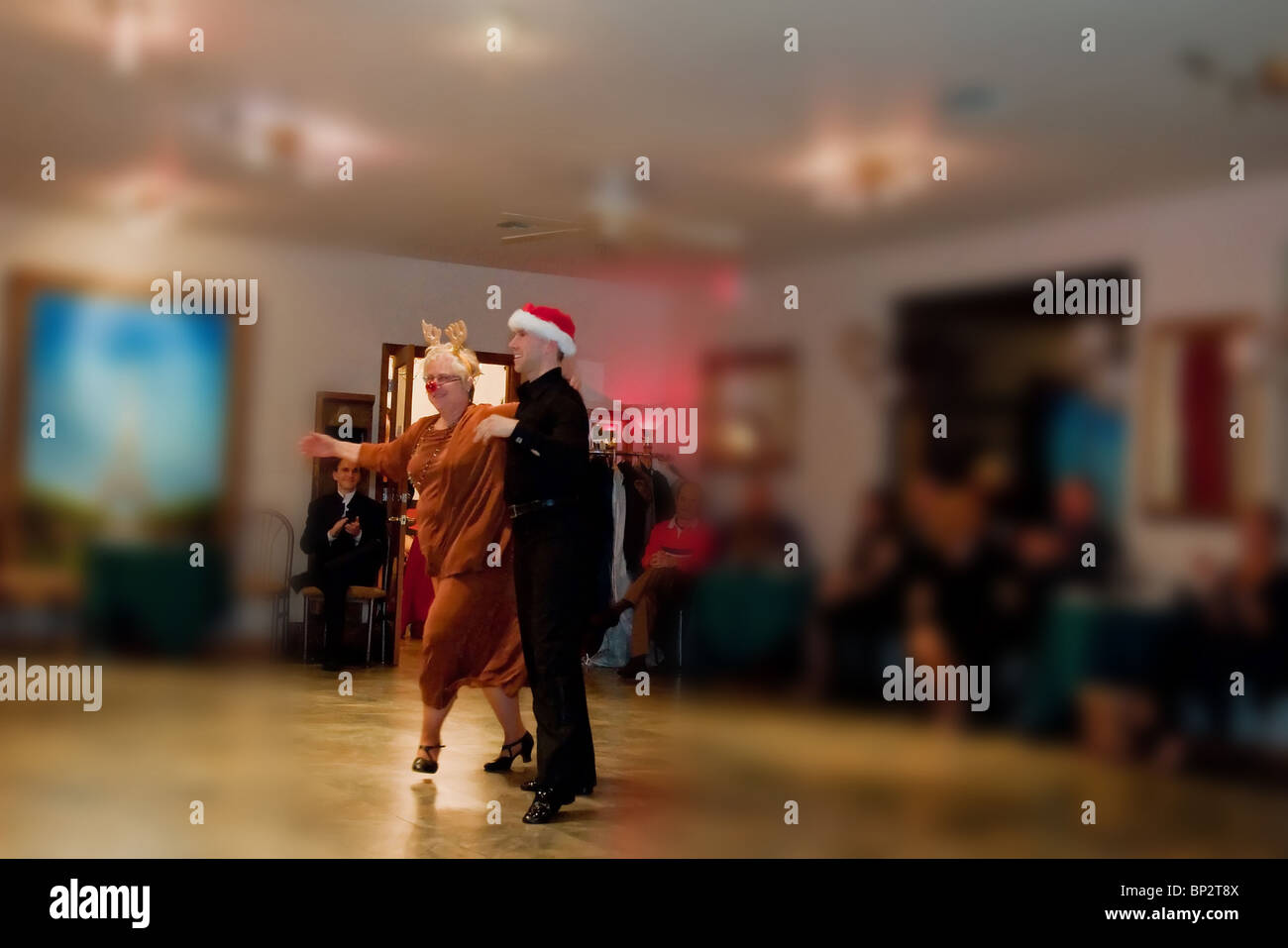 Senior citizen lady with Rudolph costume wearing a bright red nose, dances in a ballroom dance event. - Stock Image