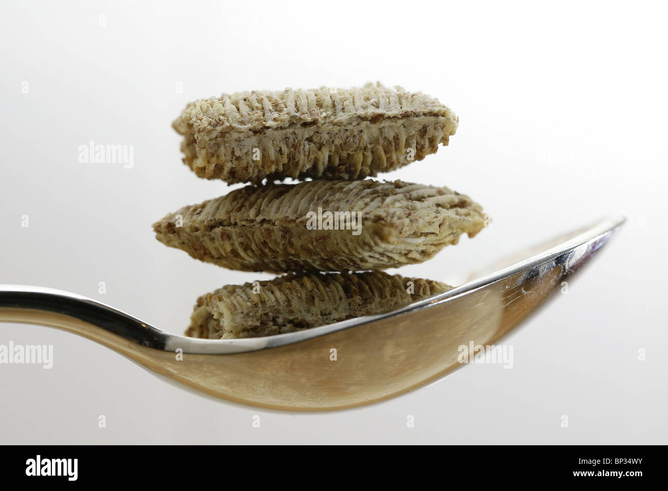 Three Bitesize Shredded Wheat's balanced in a silver spoon.  Picture by James Boardman. - Stock Image