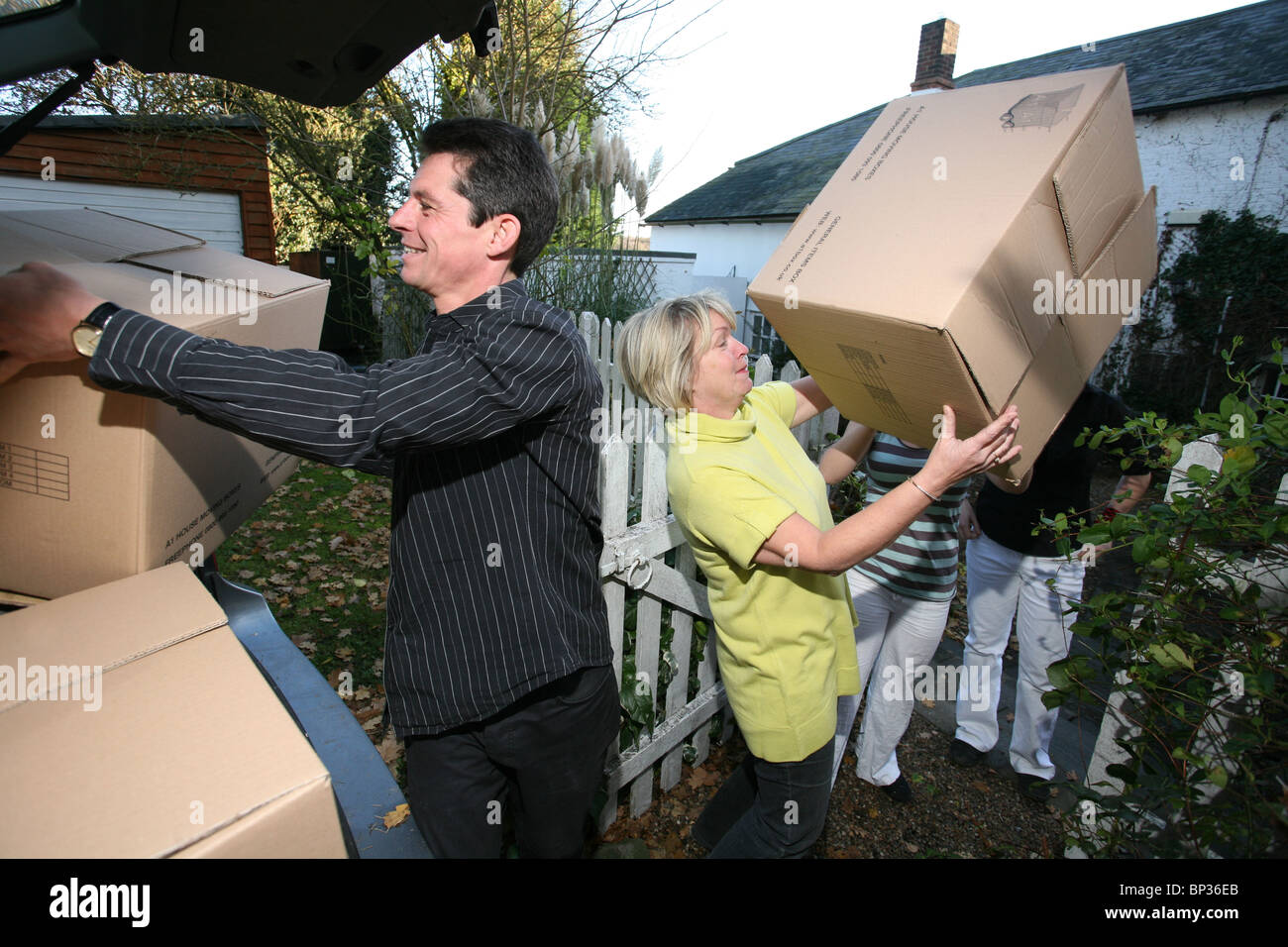 Image shows a family moving house, loading boxes into their car. Photo:Jeff Gilbert - Stock Image