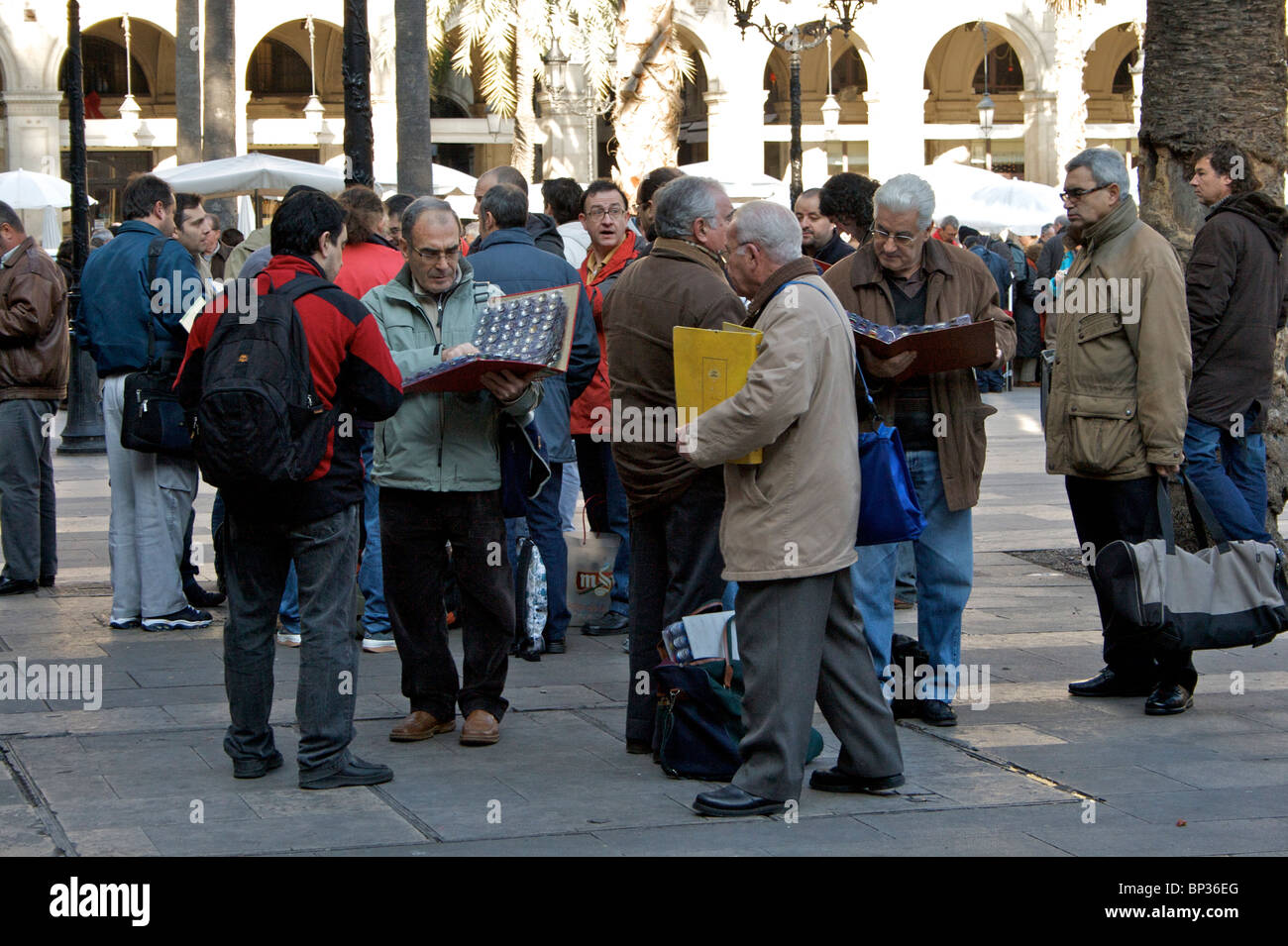 Coin enthusiasts and collectors of cava caps meet each Sunday at the coin and medal market in Placa Reial in Barcelona - Stock Image