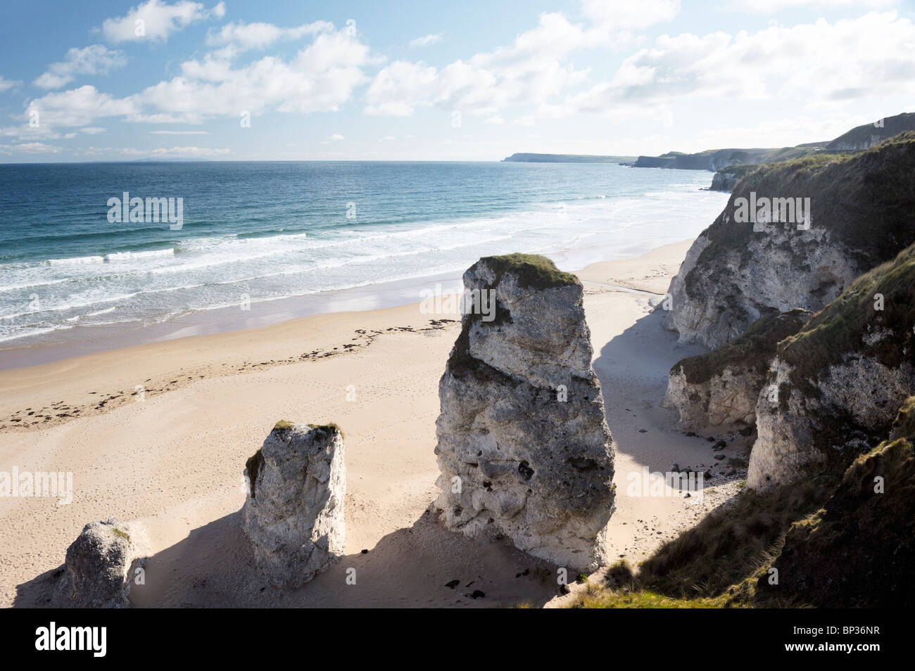 Deserted beach with footprints at the White Rocks between Portrush and Bushmills, Northern Ireland. Eroded limestone - Stock Image