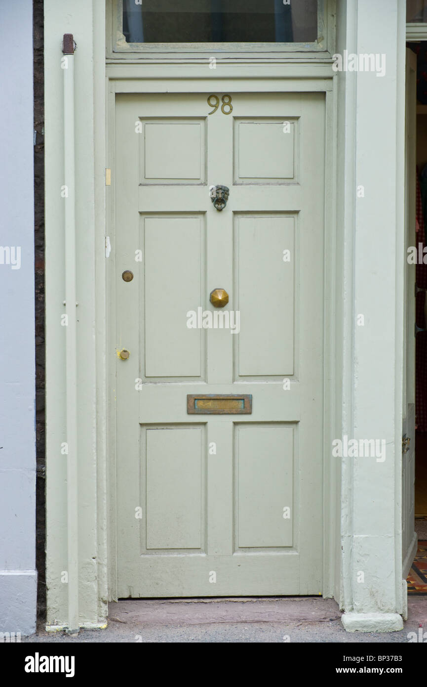 Gray painted wooden paneled front door no. 98 with brass letterbox ...