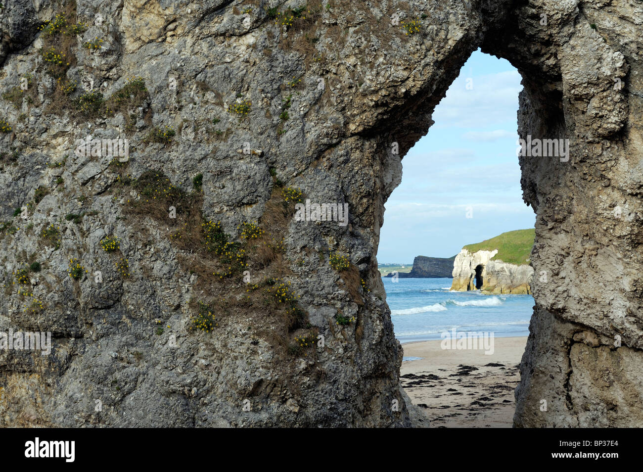 Eroded natural sea arch in limestone cliffs at the White Rocks between Portrush and Bushmills, Northern Ireland - Stock Image