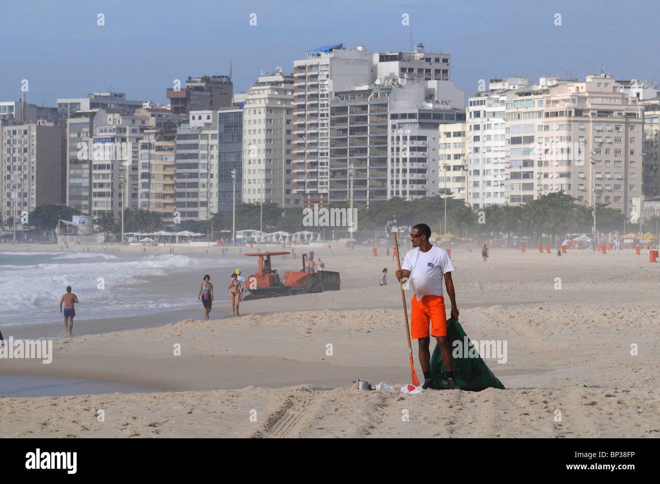 A worker cleaning up the famous beach of Copacabana in Rio de Janeiro, Brazil - Stock Image