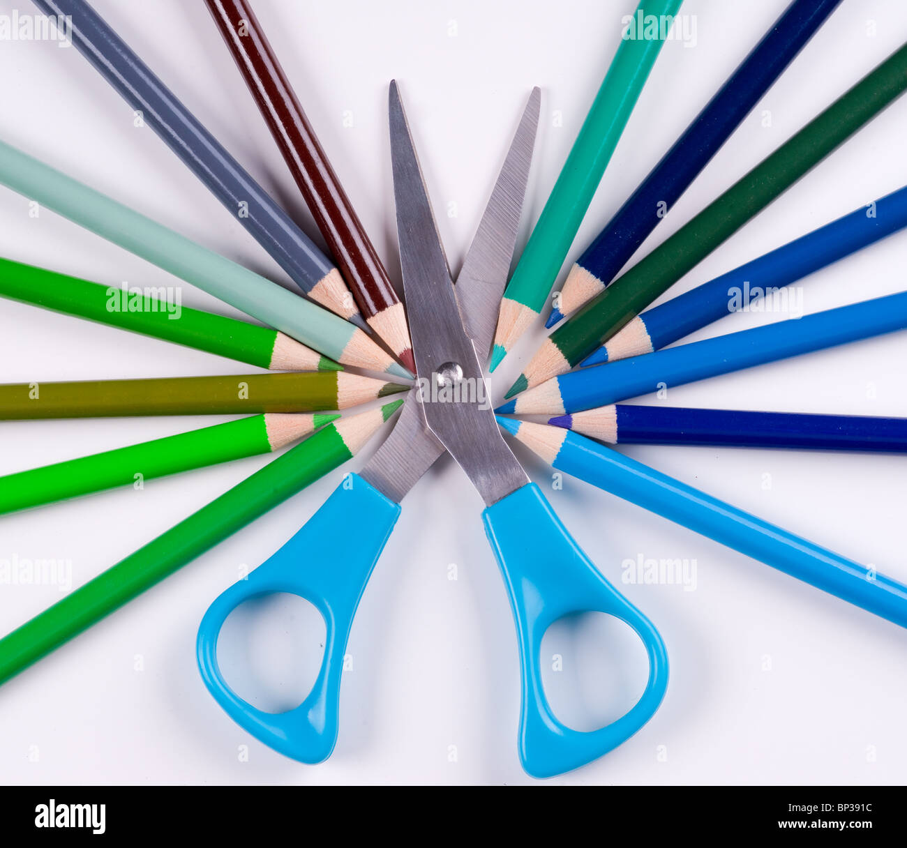 Blue scissors surrounded by the pencils of cool colors - Stock Image