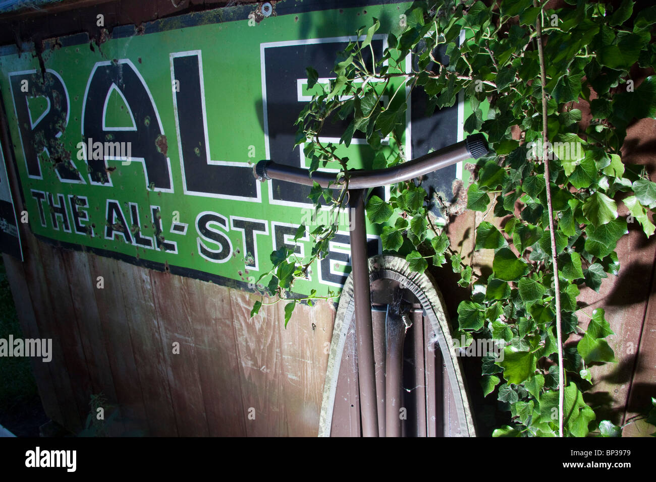 An old stove enamel advertising sign Raleigh The All-Steel Bicycle overgrown by ivy and under lit - Stock Image