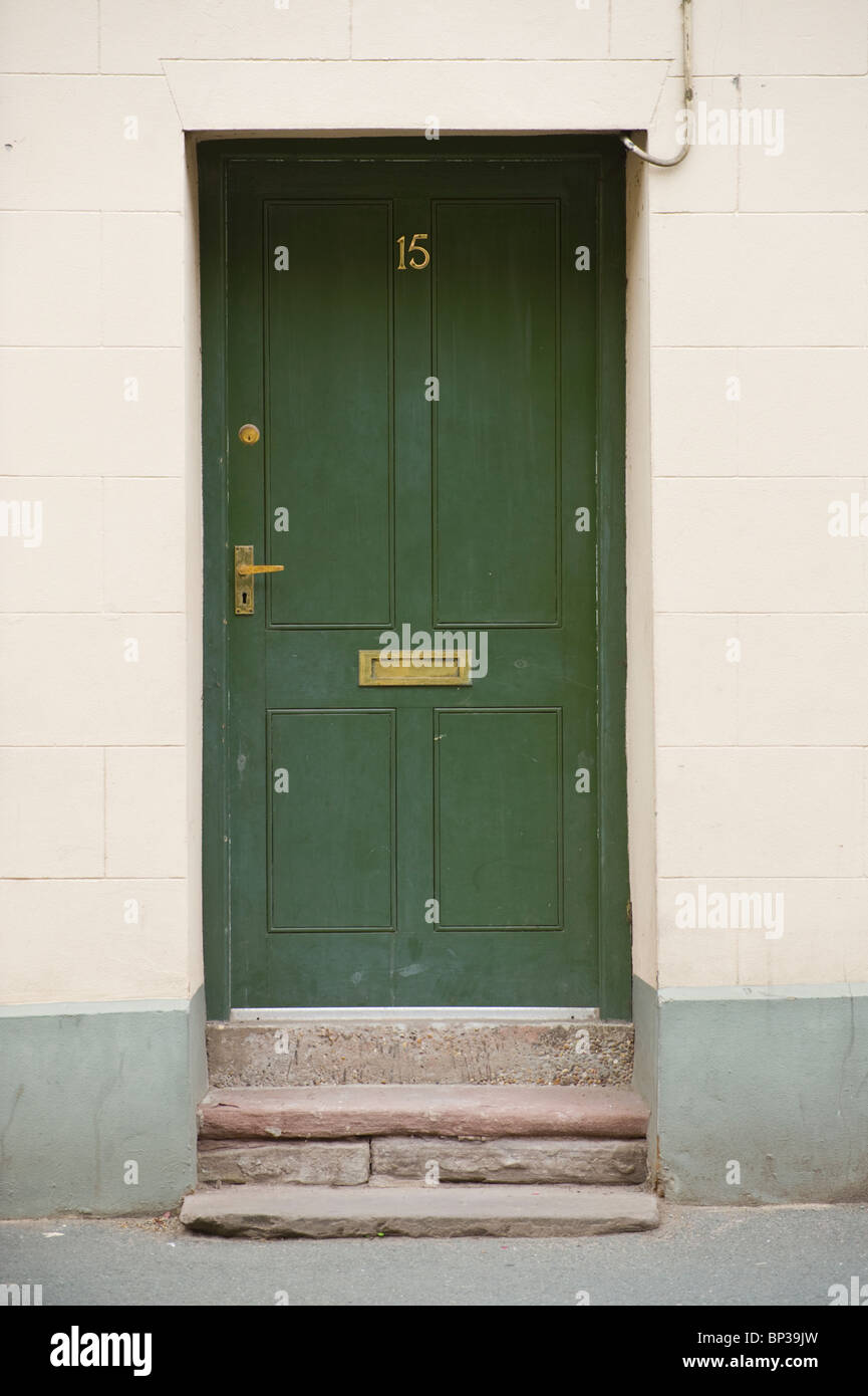 Painted green wooden paneled front door no. 15 with brass handle ...