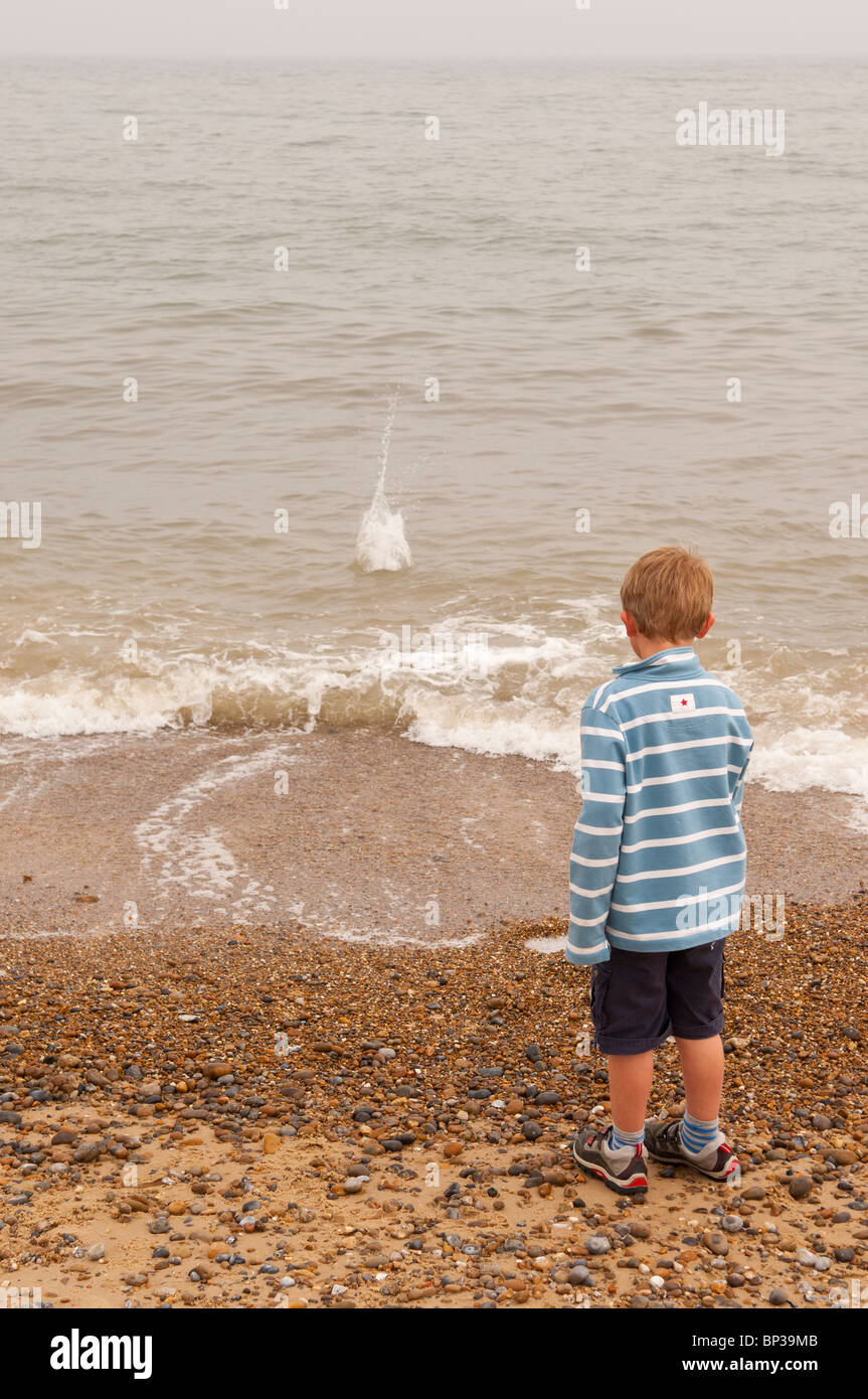 A MODEL RELEASED picture of a 6 year old boy throwing stones into the sea on a UK beach - Stock Image