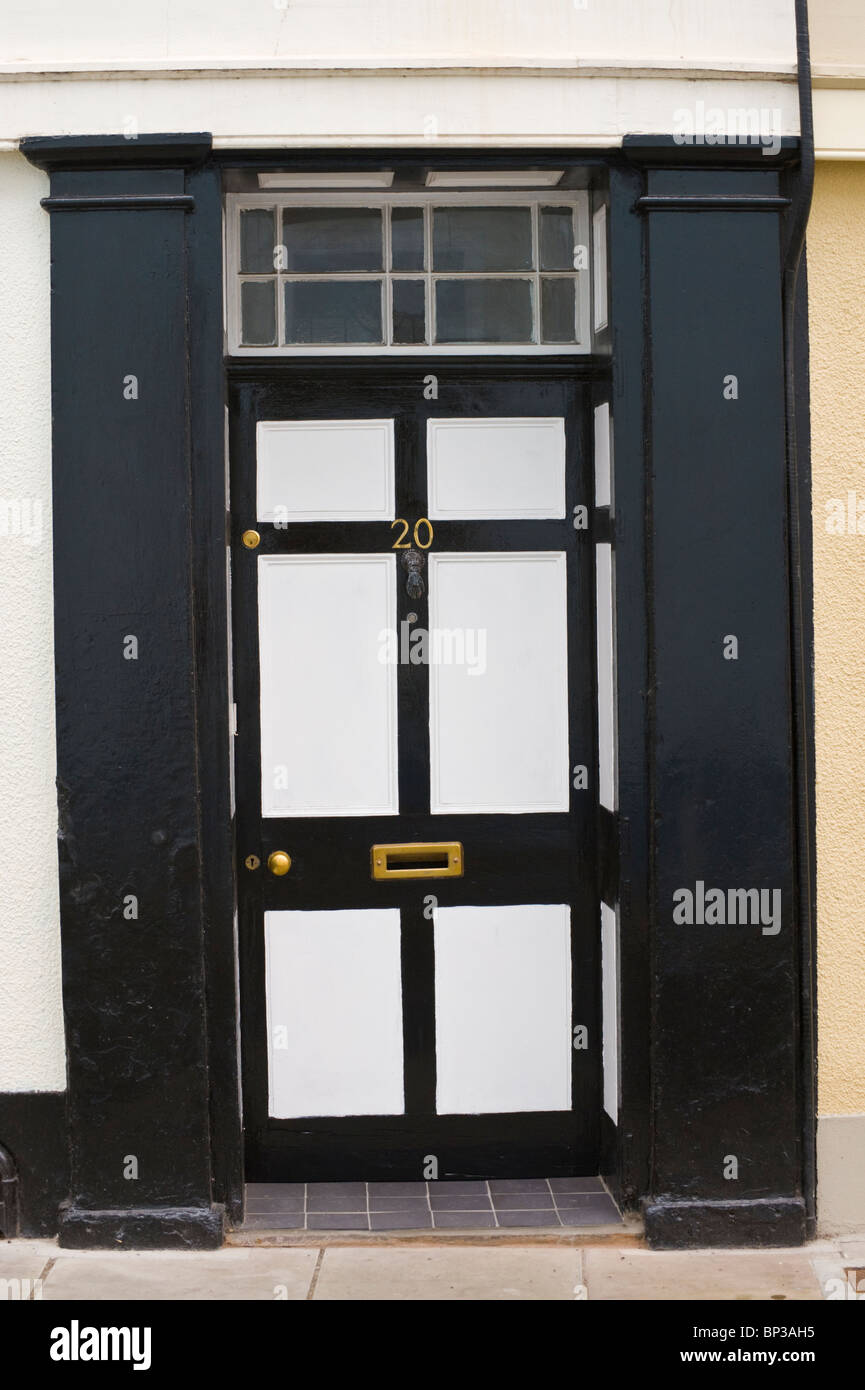 White and black painted wooden paneled front door no. 20 with brass knob letterbox and black surround of period - Stock Image