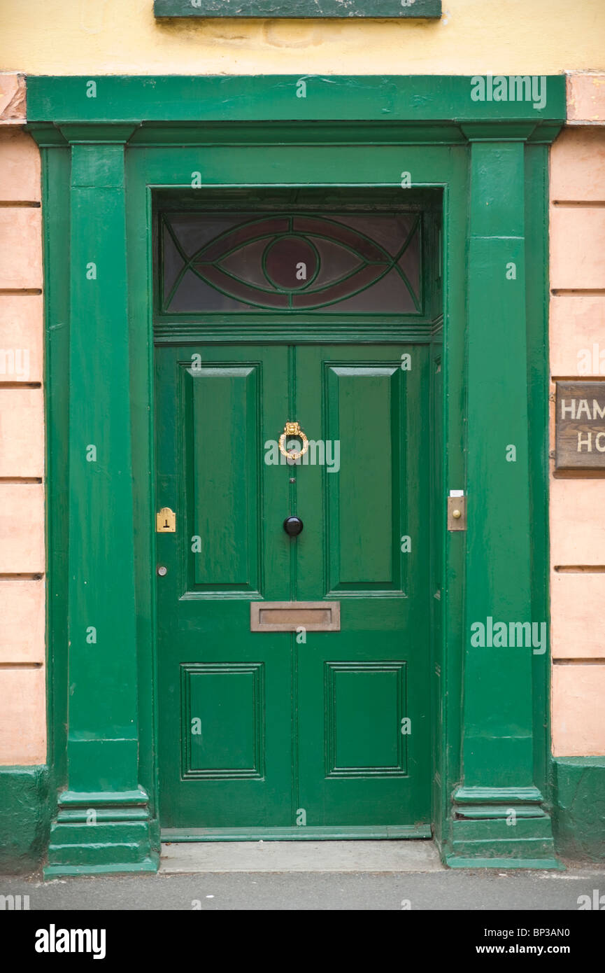 Green painted wooden paneled front door with brass knocker letterbox ...
