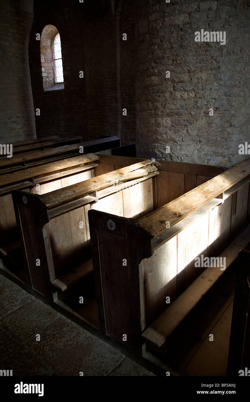 Empty pews in church bathed in sunlight - Stock Image