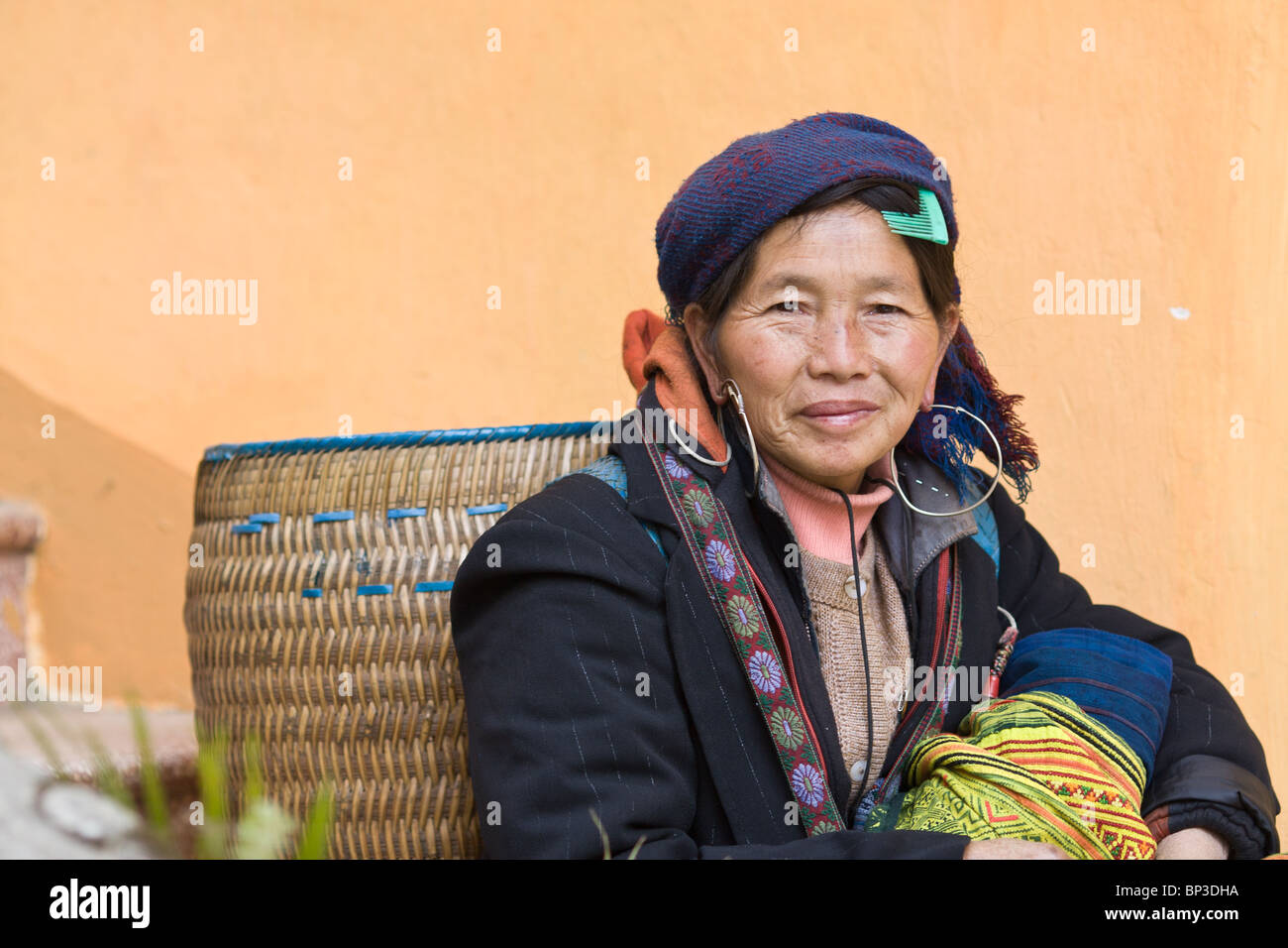 a  Black Hmong woman sitting with her basket next to a colorful wall in Sapa, vietnam - Stock Image