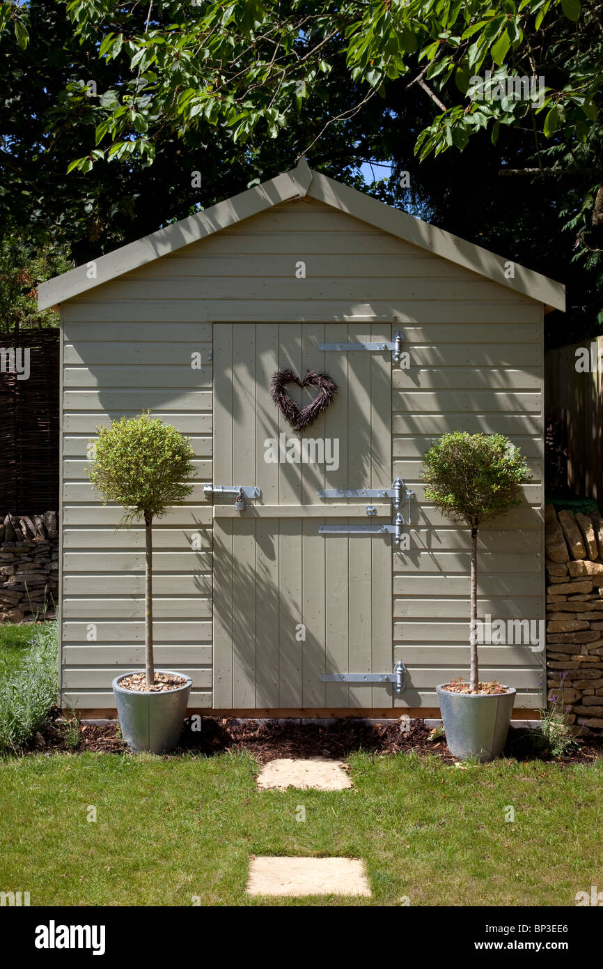 Pretty wooden garden tool shed with bay standard trees either side the door with heart shaped wreath on door - Stock Image