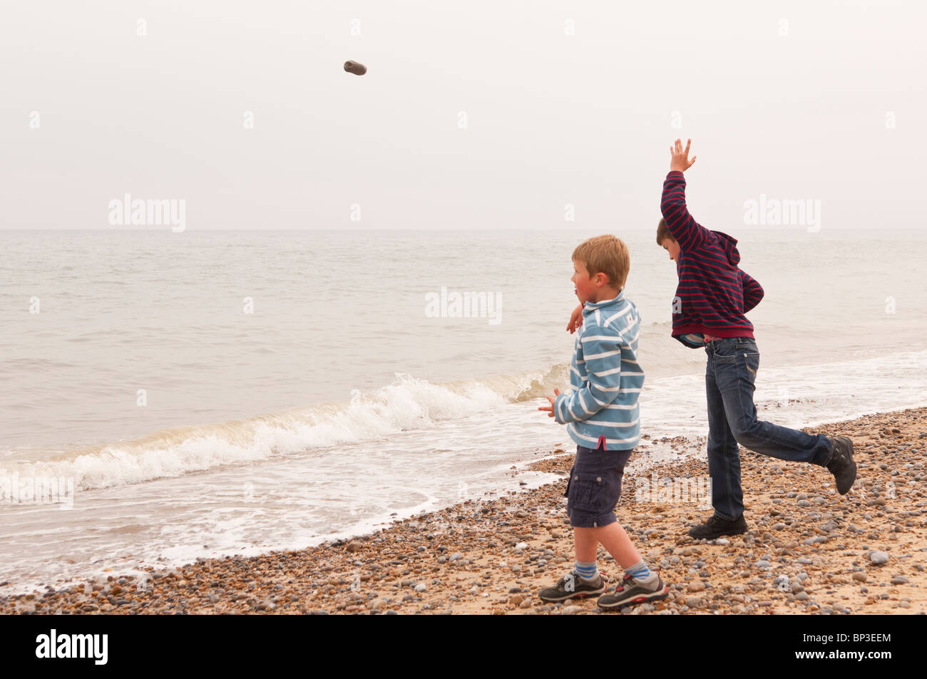 A MODEL RELEASED picture of two boys ( 6 & 10 ) throwing stones into the sea on a UK beach - Stock Image