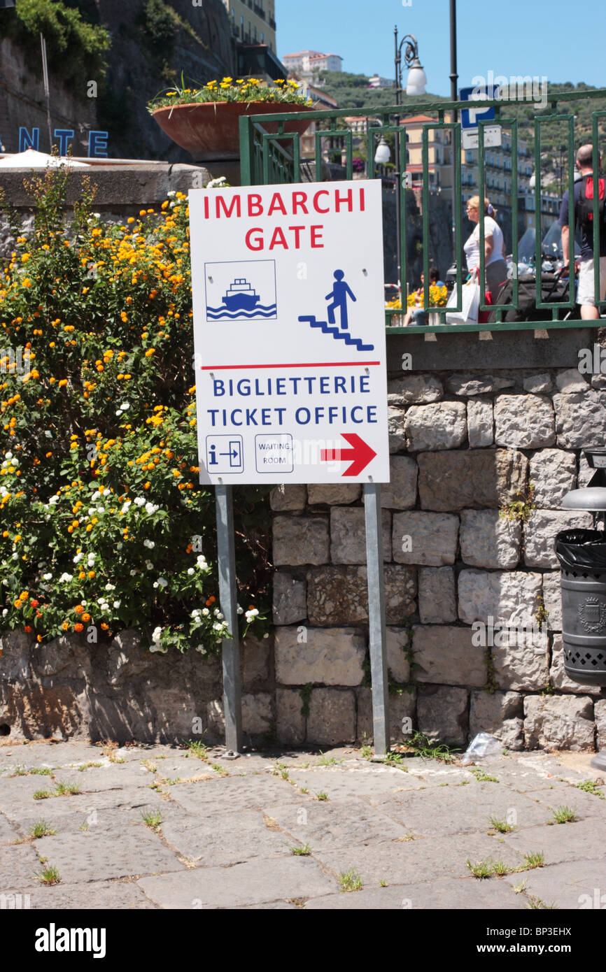 Sign giving directions to the ferry ticket office and embarkation gate Sorrento Italy - Stock Image