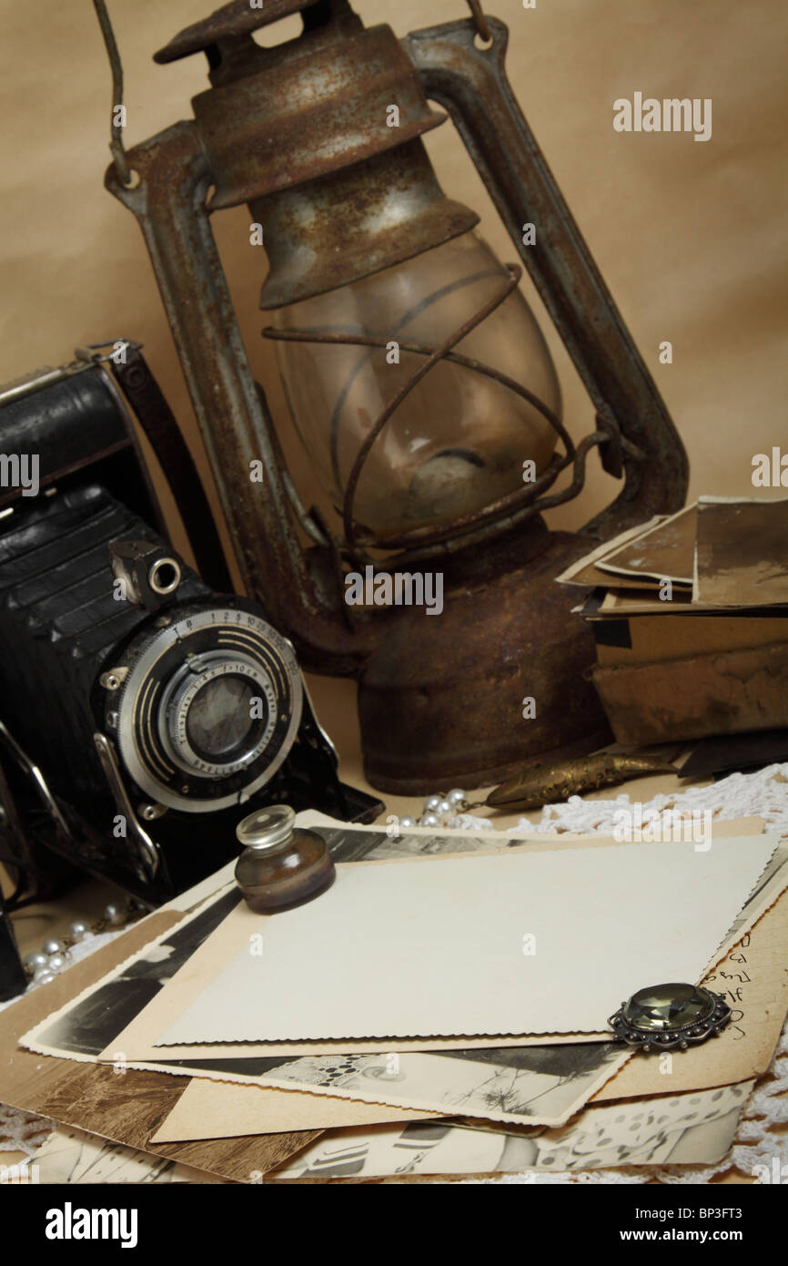 Retro camera, kerosene lamp and old photos on the knitted cloth - Stock Image