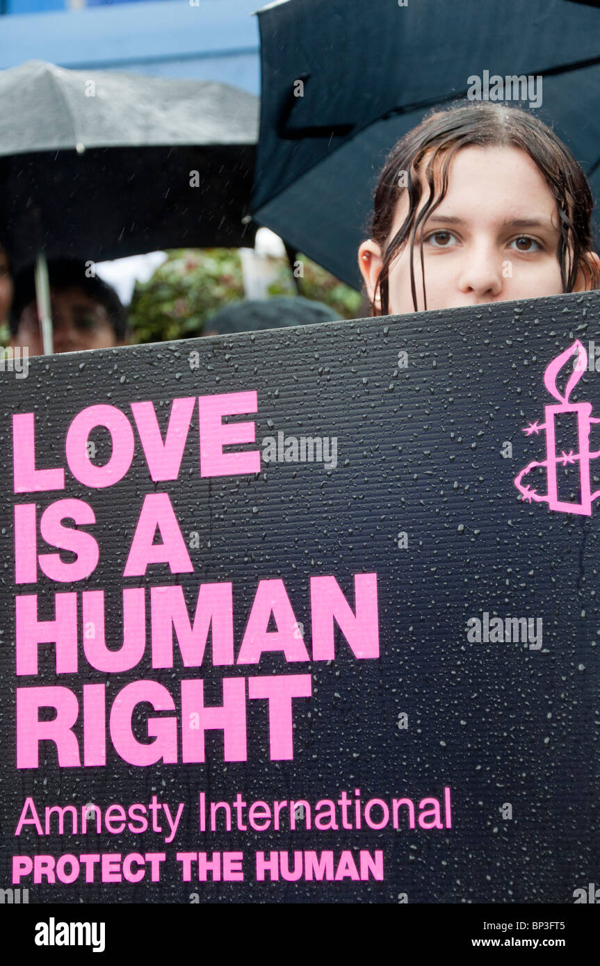 Young girl holds 'love is a human right' placard at demonstration. - Stock Image