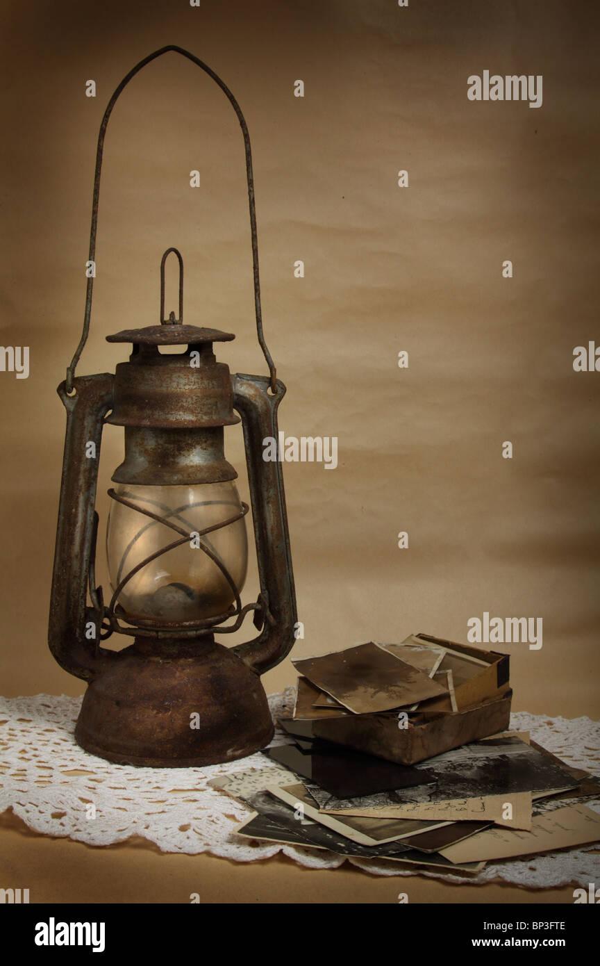 Old kerosene lamp and photos on the cloth - Stock Image
