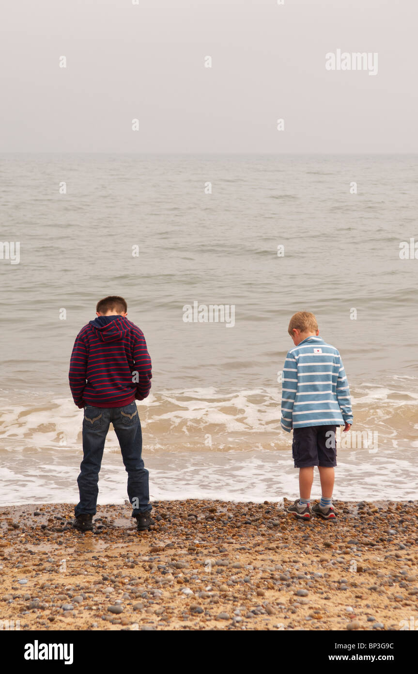 A MODEL RELEASED picture of two boys ( 6 & 10 ) standing by the sea on a UK beach - Stock Image