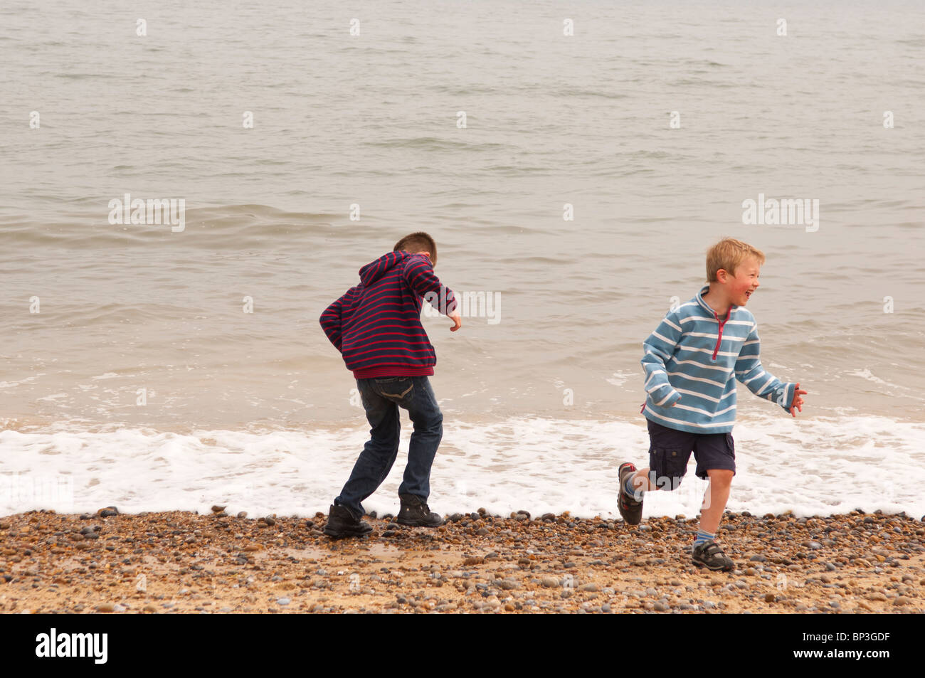 A MODEL RELEASED picture of two boys ( 6 & 10 ) playing by the sea on a UK beach - Stock Image