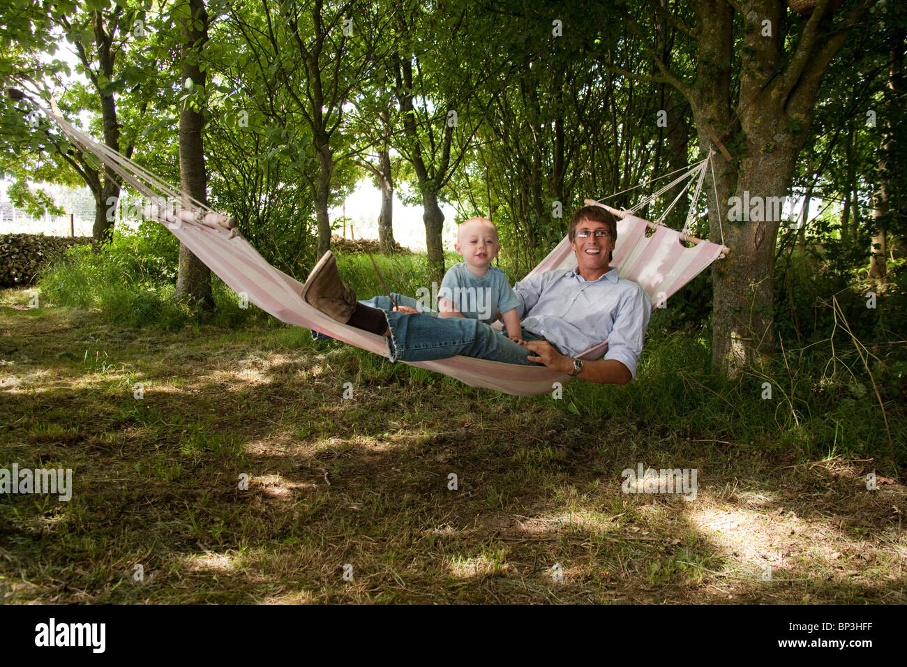16 month old baby boy and his uncle having fun on a garden hammock ...
