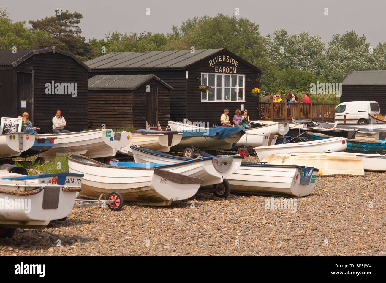 The Riverside tearoom with boats in the foreground at Orford , Suffolk , England , Great Britain , Uk - Stock Image