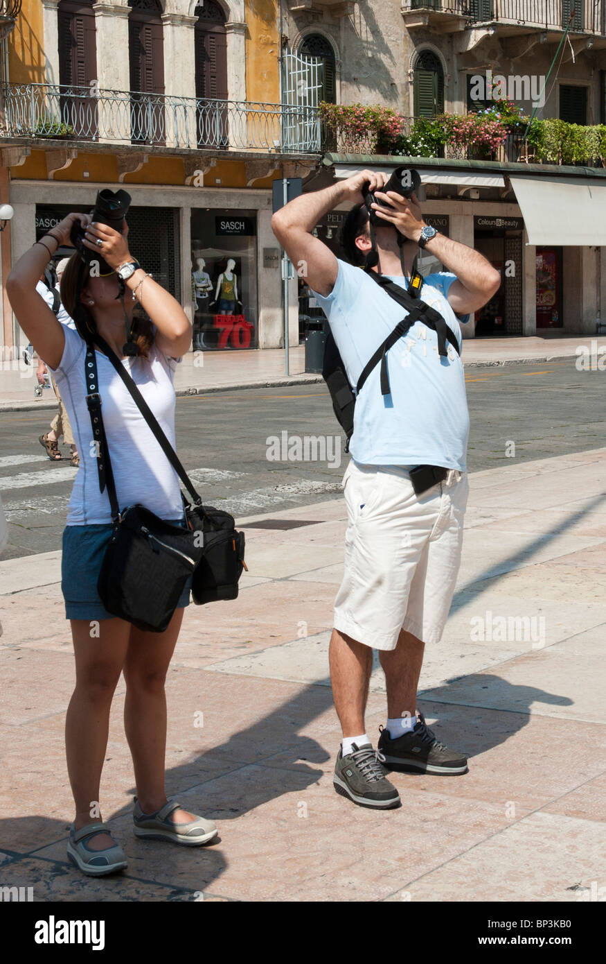 Two tourists take pictures in Piazza Erbe Verona Italy - Stock Image
