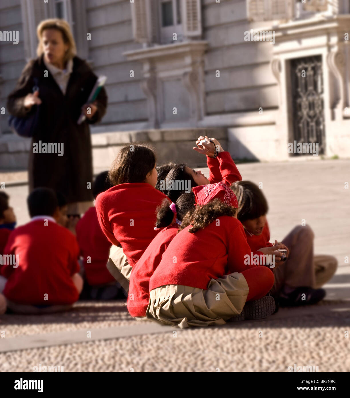 Schoolchildren and teacher visit The Royal Palace in Madrid, Spain during an educational school outing. - Stock Image
