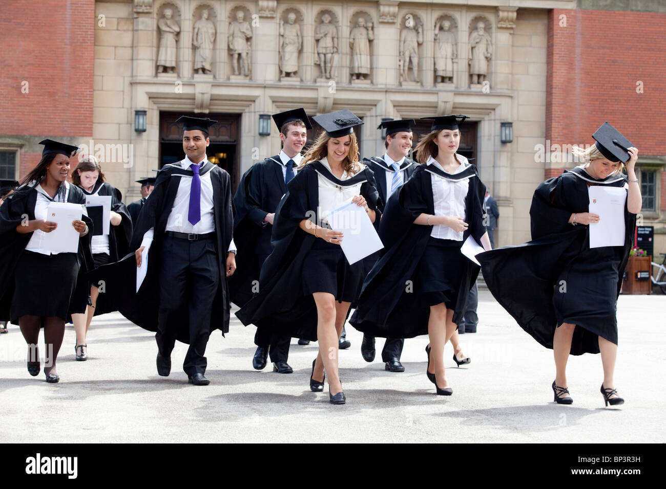 Graduates leave the Great Hall after a degree ceremony at Birmingham University UK - Stock Image
