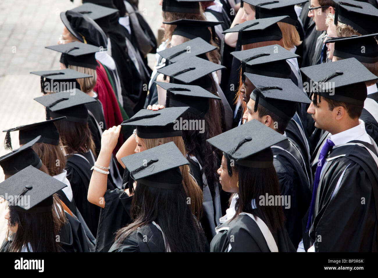 Graduates wait to be photographed after a degree ceremony at Birmingham University in the UK - Stock Image