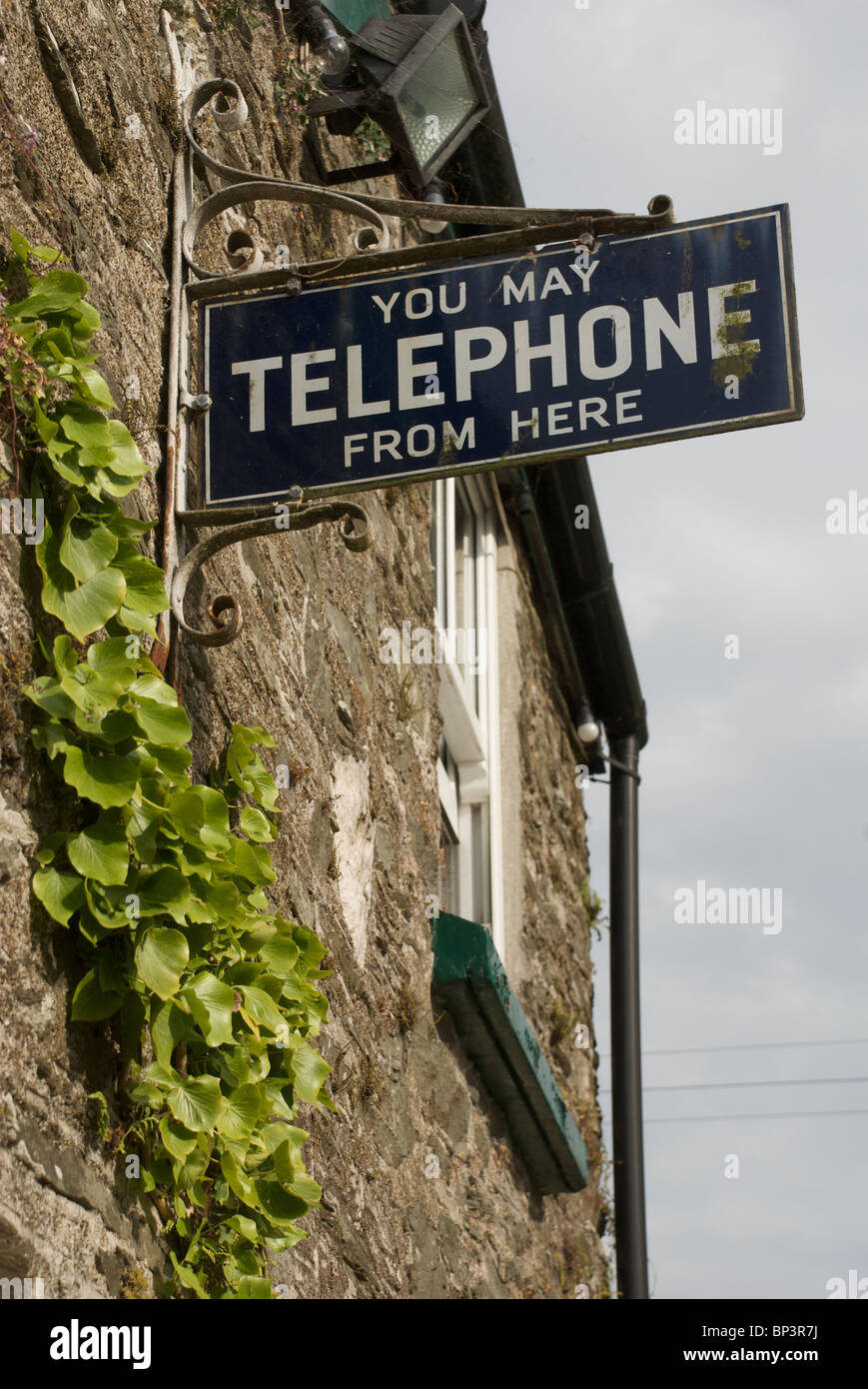 Old metal telephone access sign on a pub wall, South Hams, Devon, UK - Stock Image