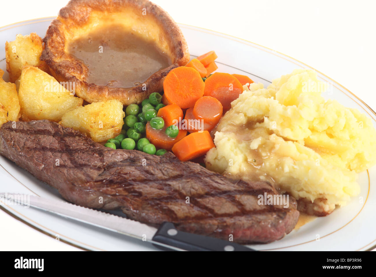 A 'pub-grub' style dinner of steak, mixed veg, roasted and mashed potatoes, yorkshire pudding and gravy, - Stock Image