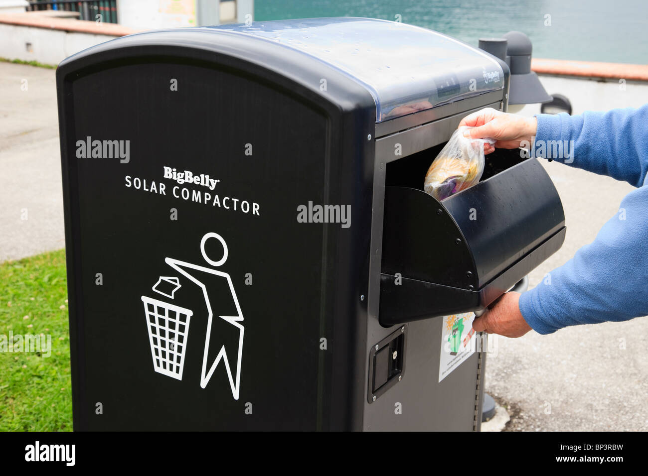Person throwing rubbish into a BigBelly Solar powered litter compactor bin for compressing trash - Stock Image