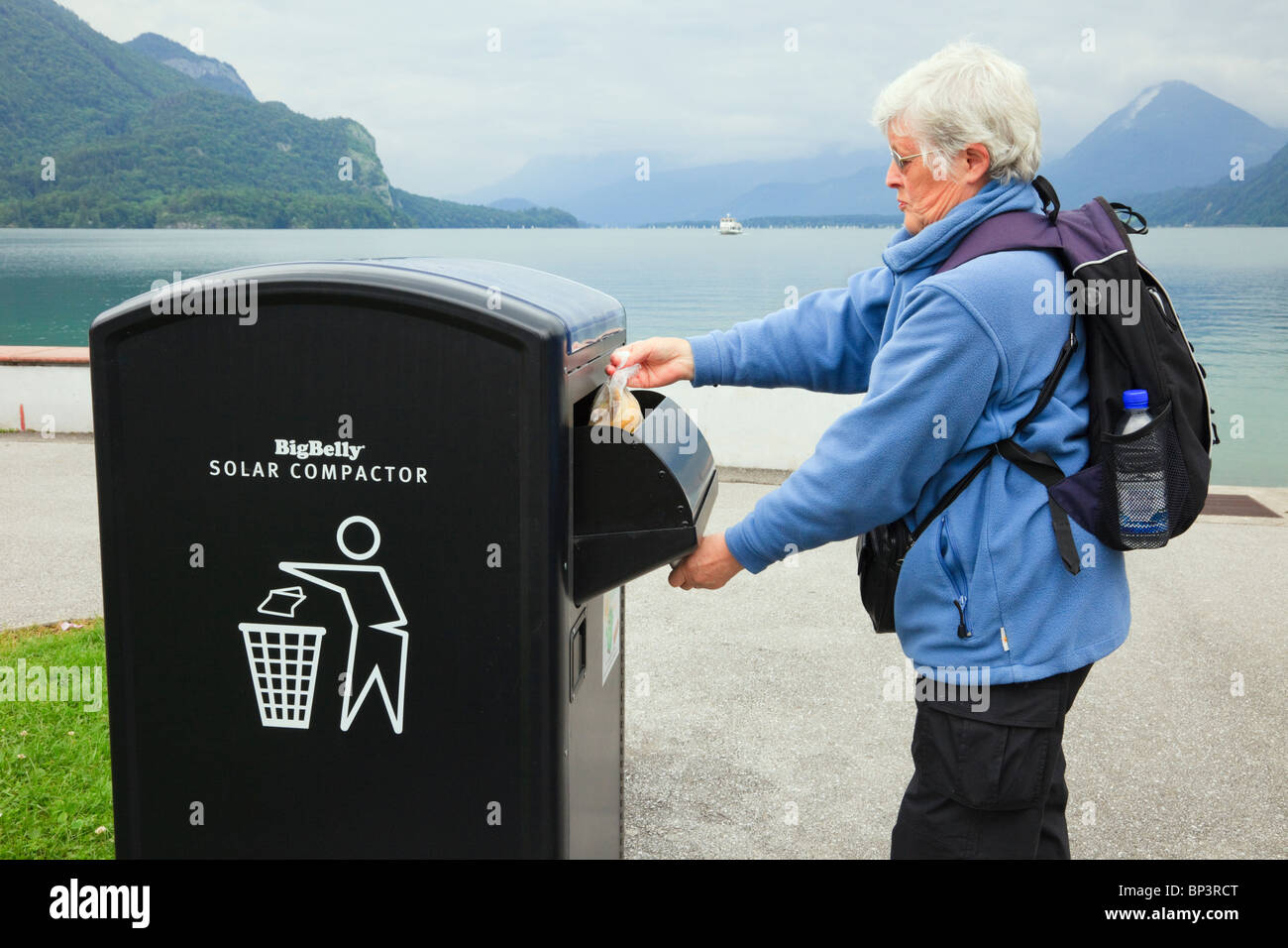Woman throwing rubbish into a BigBelly Solar powered litter compactor bin for compressing trash - Stock Image