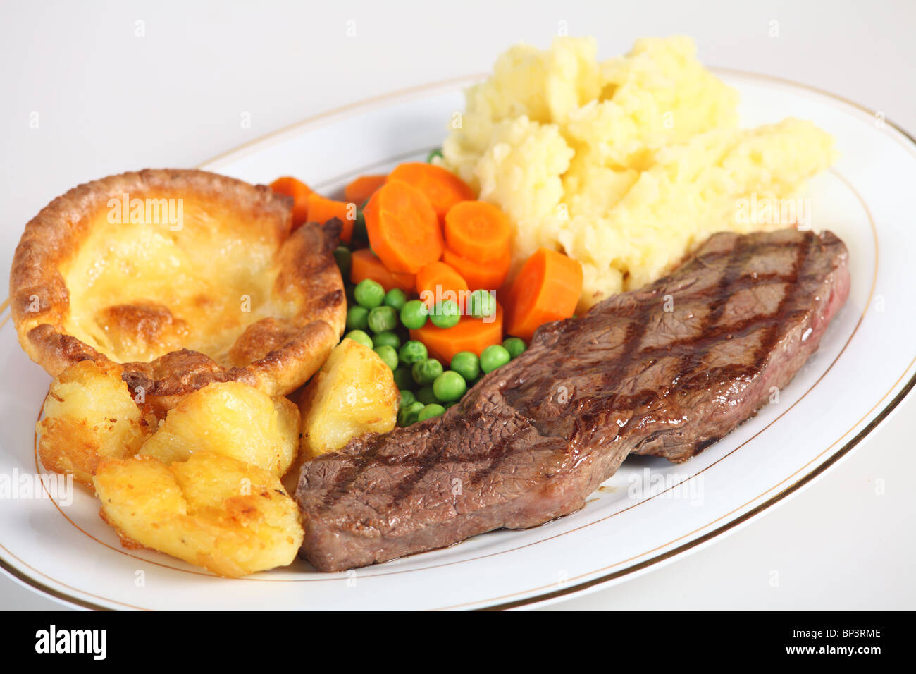 A traditional pub-grub style British meal of rump steak, mixed veg, mashed and roasted potatoes and - Stock Image