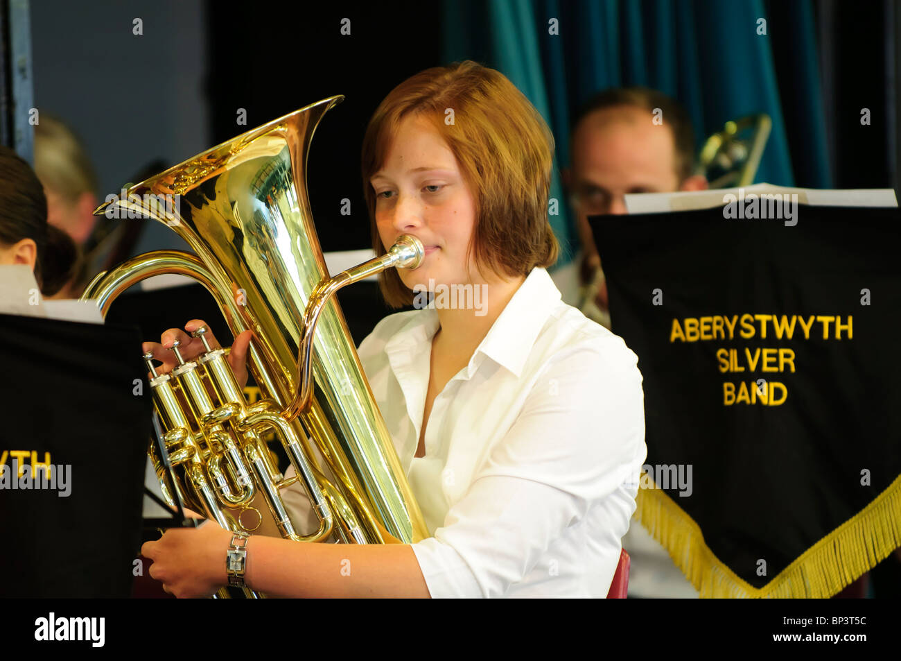 Brass band or Silver band- a young woman musician playing french horn, Aberystwyth Wales UK - Stock Image