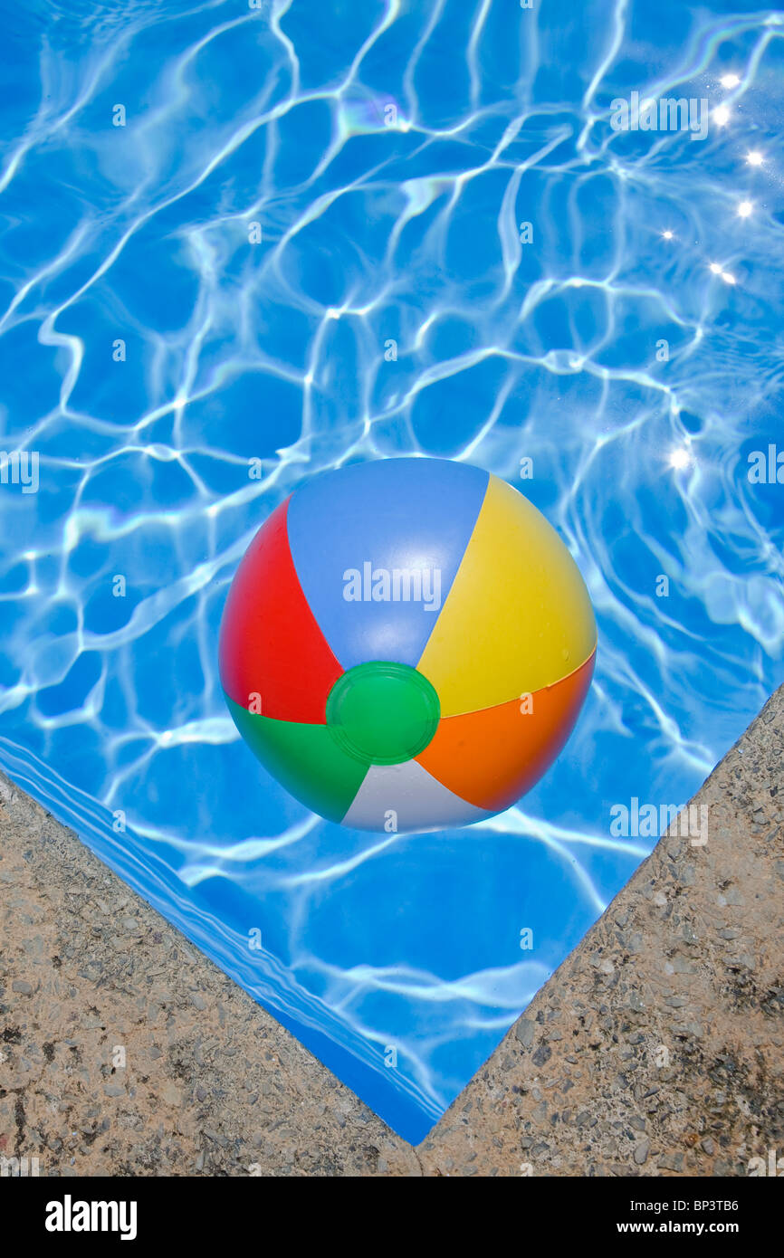 Bright blue swimming pool withj a beachball in the corner - Stock Image