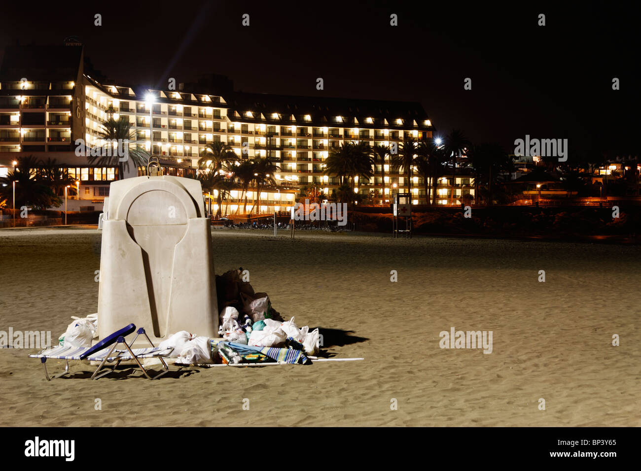 Overflowing rubbish container on beach in Spain with large hotel in background - Stock Image