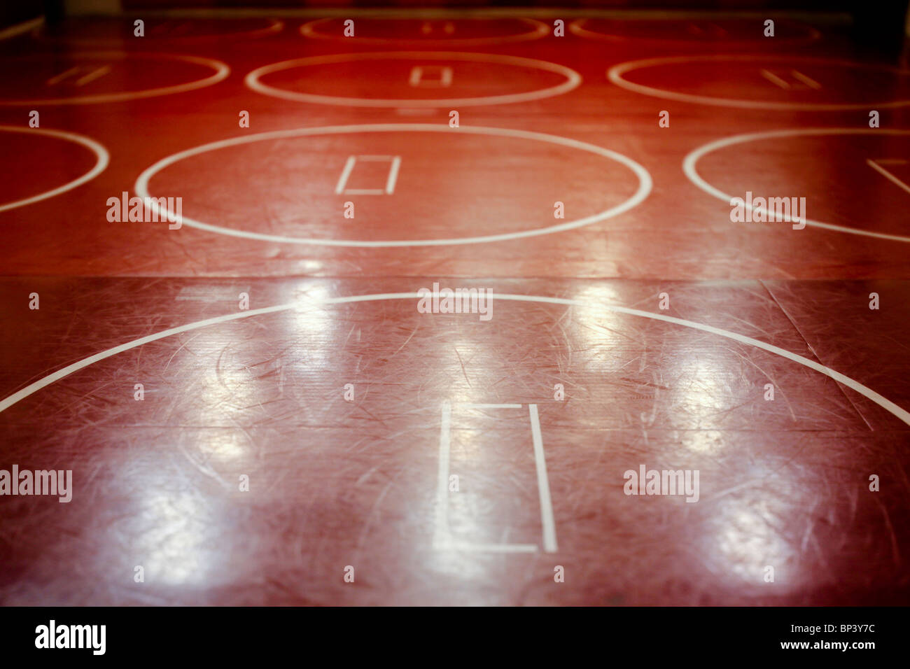 Well worn red school wrestling mat in a gym. Stock Photo