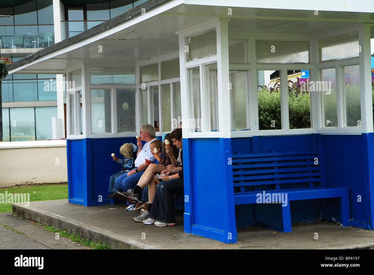 Family eating ice-creams in shelter on esplanade at Westward Ho!, Devon, UK - Stock Image