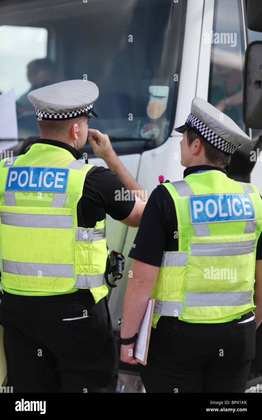UK police stopping a vehicle on a British road in hi vis vests and grey hats - Stock Image