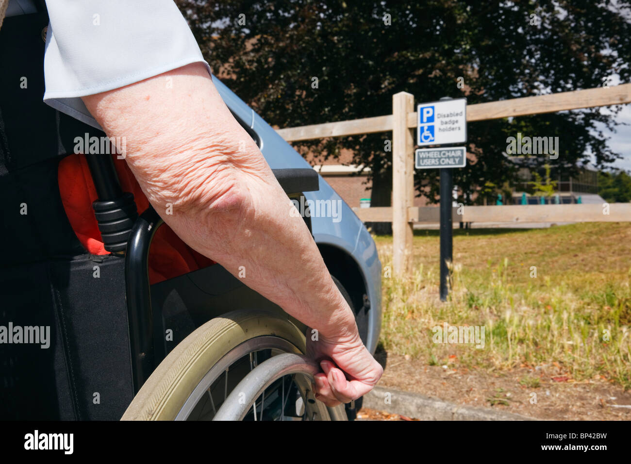 Elderly woman in a wheelchair by a car parked in blue badge disabled parking bay with sign for wheelchair users - Stock Image