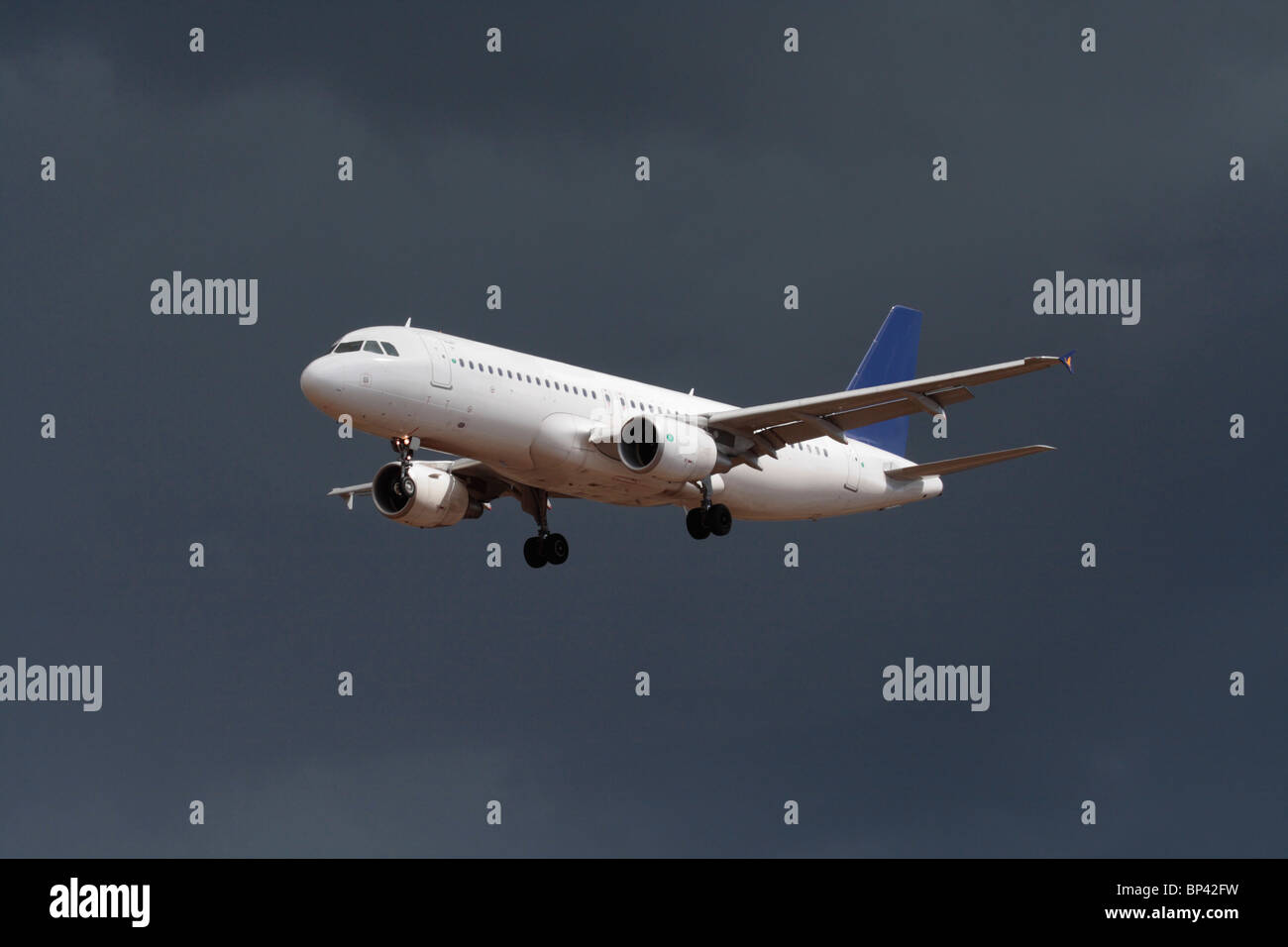 Airbus A320 passenger jet plane flying on approach against a dark cloudy sky. No livery and proprietary details - Stock Image