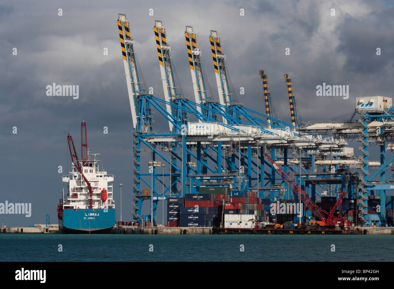 International trade by sea transport. Cargo ship at the Malta Freeport container port. Shipping, economic development - Stock Image