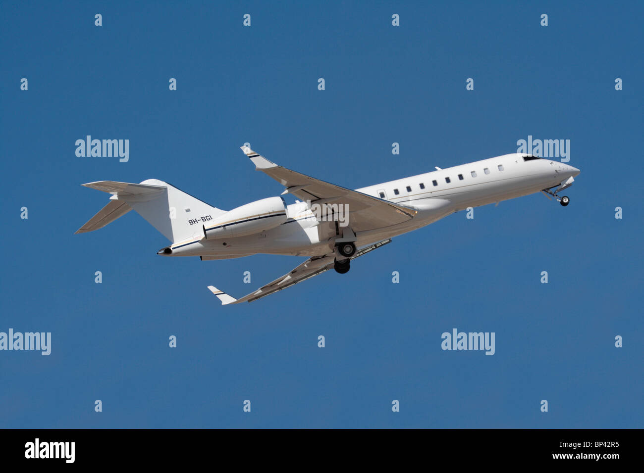 Bombardier Global Express XRS private jet operated by Comlux Aviation Malta, shown on takeoff against a clear blue - Stock Image