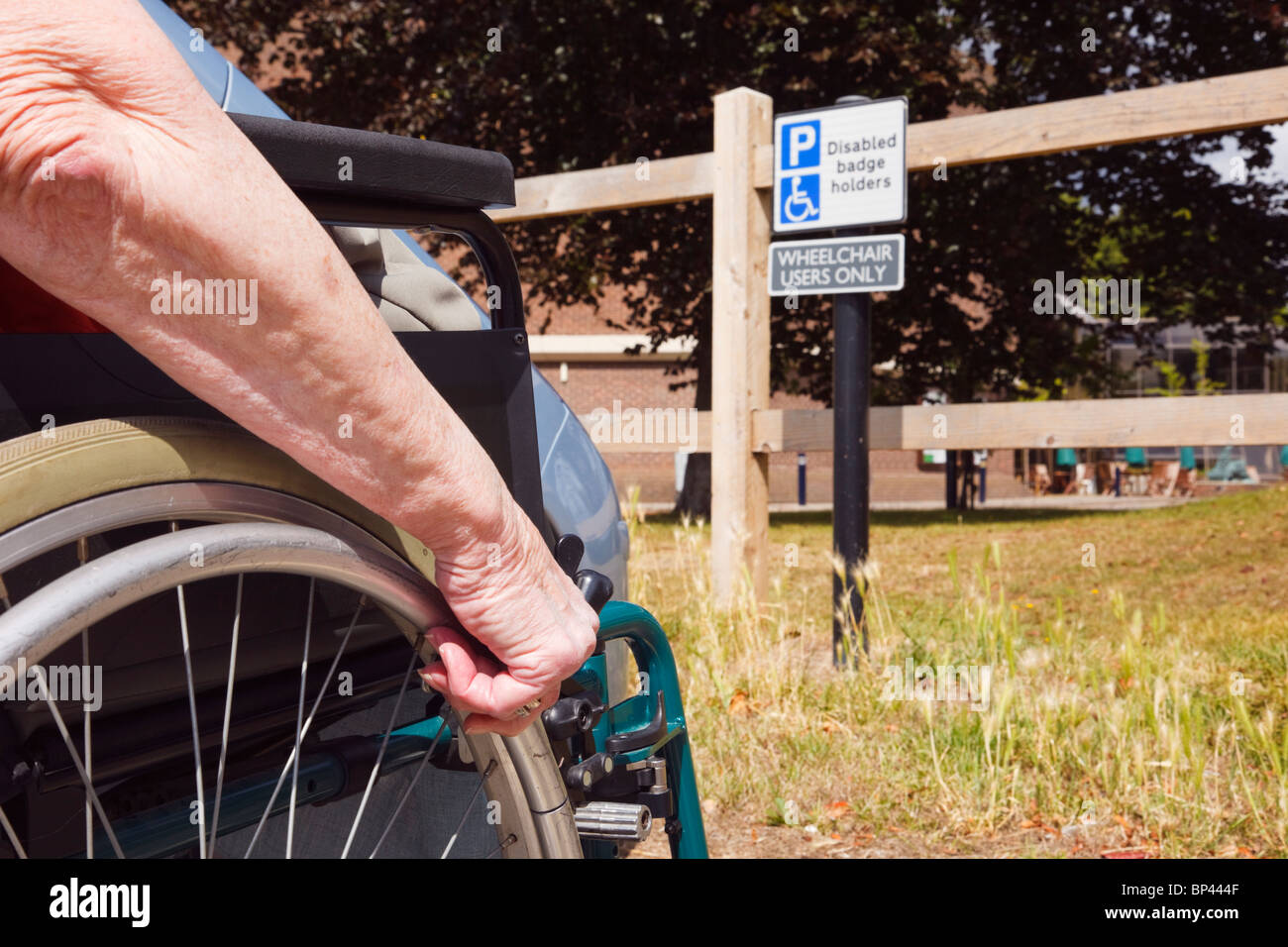 Elderly woman sitting in a wheelchair by a car parked in disabled parking bay by a sign for blue badge wheelchair - Stock Image