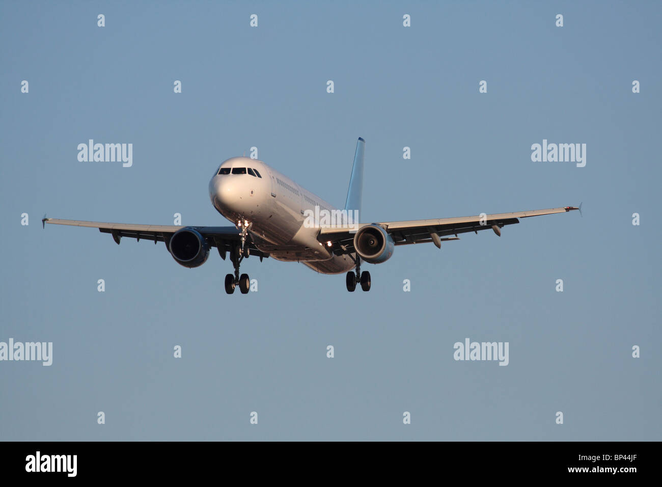Commercial air travel. Airbus A321 narrowbody passenger jet plane flying on approach in a blue sky. Front view with - Stock Image