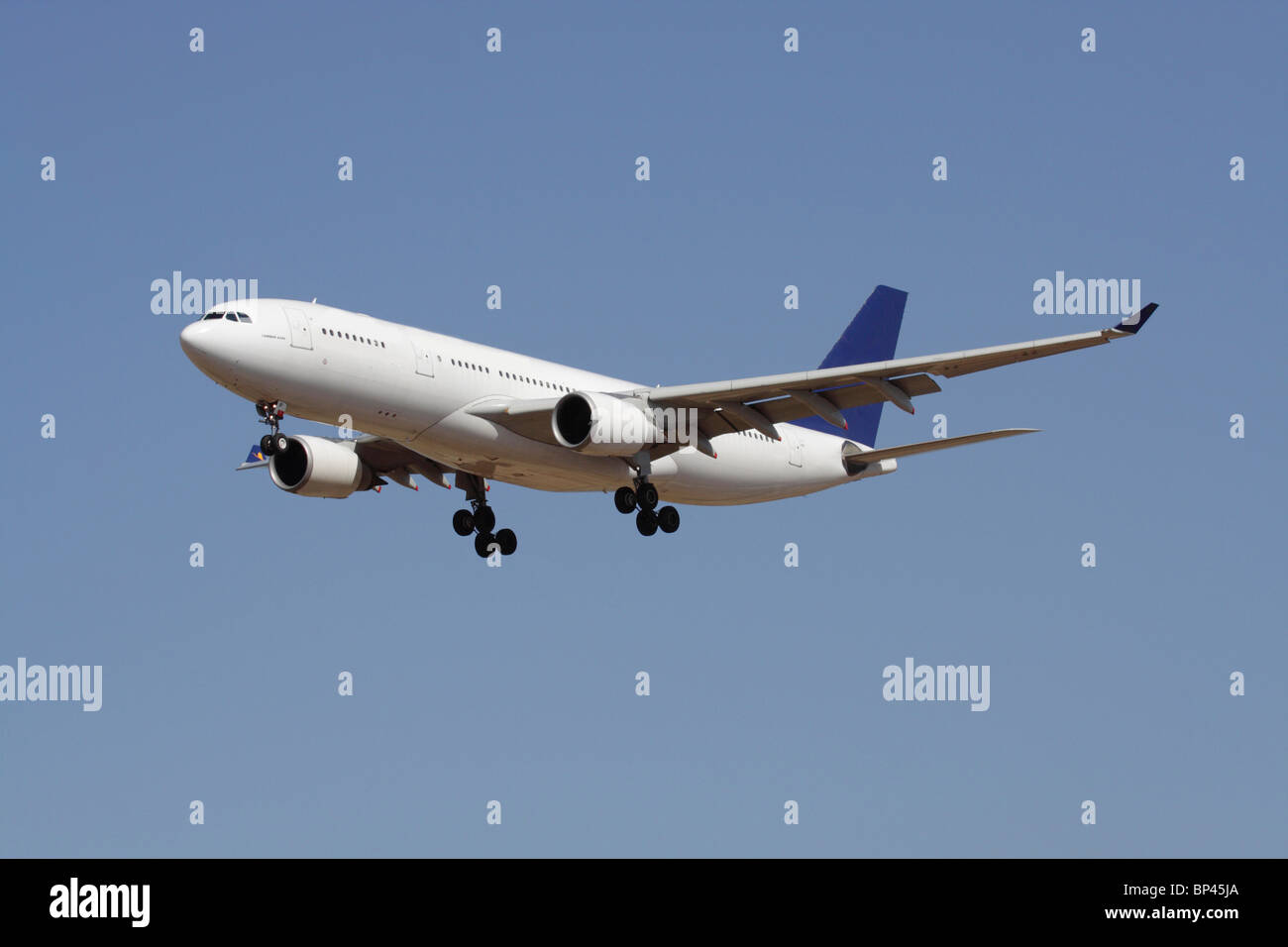 Commercial air travel. Airbus A330 long haul widebody passenger jet plane in flight against a blue sky. No livery - Stock Image