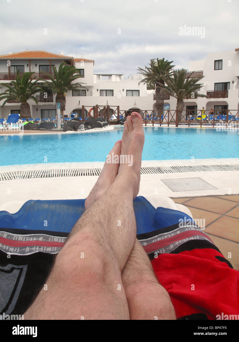 Mans feet on sunbed by pool - Stock Image